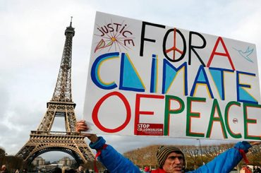 """Jean-Baptiste Redde aka Voltuan holds a banner reading """"For a climate of peace"""" during a rally held by several Non Governmental Organisations (NGO) to form a human chain on the Champs de Mars near the Eiffel Tower in Paris on December 12, 2015 on the sidelines of the COP21, the UN conference on global warming. French hosts submit the final version of a global climate-saving pact to negotiators at UN Conference on december 12. The goal is for ministers to approve the agreement by the end of the day but that could be extended one more day. / AFP / FRANCOIS GUILLOT        (Photo credit should read FRANCOIS GUILLOT/AFP/Getty Images)"""
